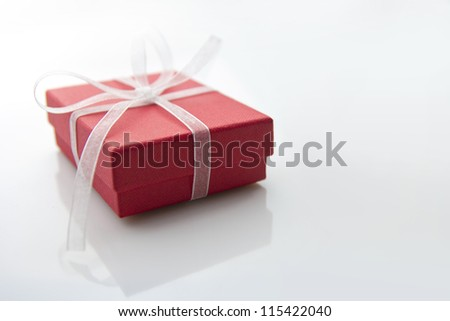 red gift box on white table - stock photo