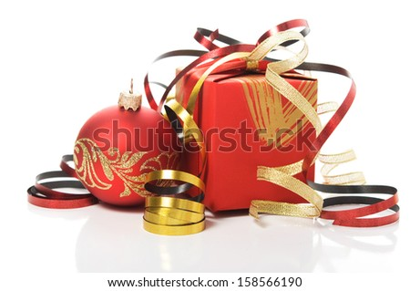 Red gift box with colorful ribbons and xmas baubles on white background - stock photo