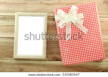 Red gift box with empty wooden picture frame on wood background,concept of christmas and Important day.