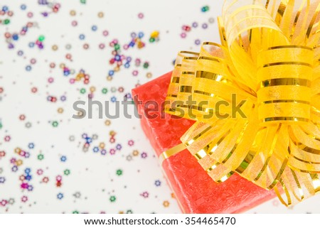red gift box with gold ribbon and bow on white paper background.