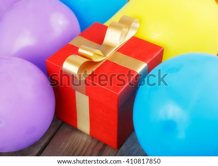 Red gift box with gold ribbon in balloons on the wooden table close up - stock photo