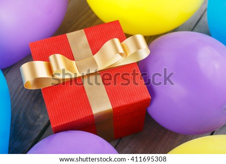 Red gift box with gold ribbon in balloons on the wooden table close up, top view  - stock photo