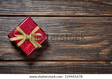 Red gift box with golden ribbon on wooden background - stock photo