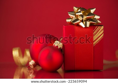Red gift box with golden ribbons and xmas baubles on red background. Merry christmas. - stock photo