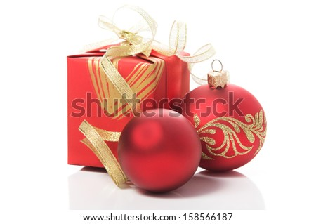 Red gift box with golden ribbons and xmas baubles on white background