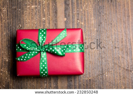 Red gift box with green ribbon with polka dots on a wood background.