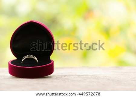 Red gift box with ring on background of greenery and flowers. Selective focus, toned image, film effect, macro, close-up - stock photo