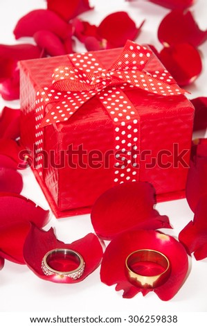 Red gift box with wedding ring and red rose petals.