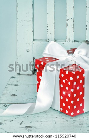 Red gift box with white bow on a light blue background - stock photo