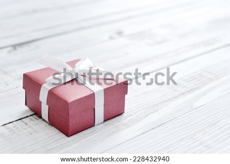 Red gift box with white ribbon over white wooden background - stock photo