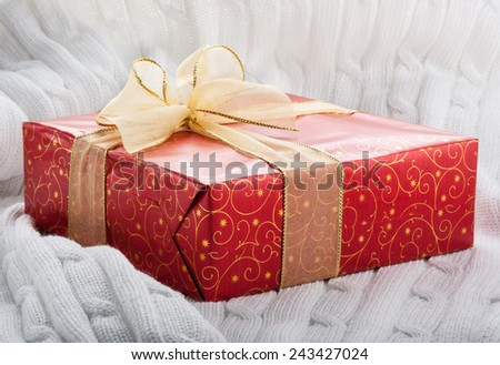 Red gift box with yellow ribbon on a white knitted background.