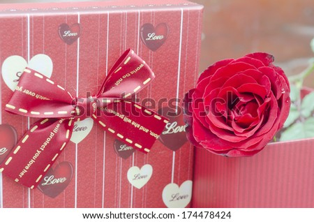 Red gift boxes and rose on wooden background