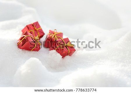 Red gift boxes on the snow. A gentle winter christmas background