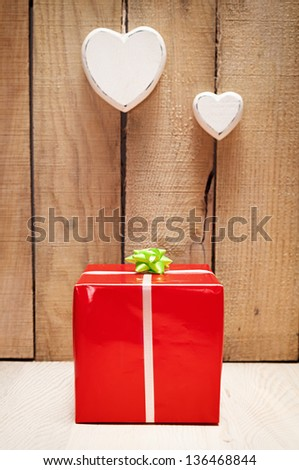red gift package in front of a wooden wall with two heart hanged - stock photo