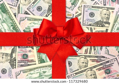 red gift ribbon bow over american dollars. money background. shopping gift card concept - stock photo