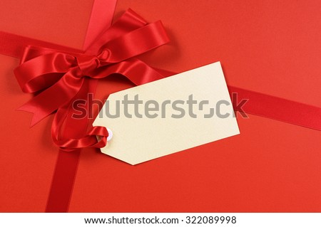 Red gift wrap background, ribbon and bow with blank tag or label  - stock photo