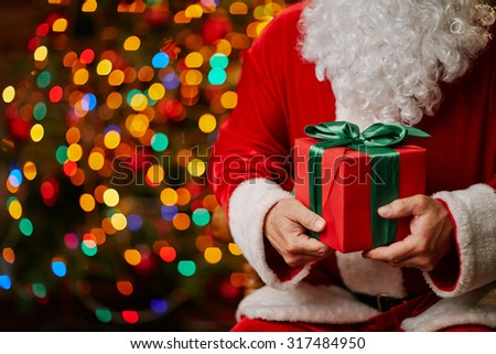 Red giftbox bound by silk green ribbon held by Santa - stock photo