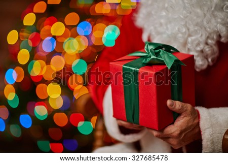 Red giftbox bound with green ribbon in Santa hands - stock photo