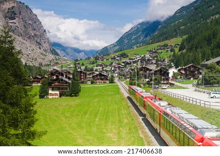 Red (glacier express) train heading through high mountain valley in switzerland alps on route from St. Moritz to Zermatt. - stock photo