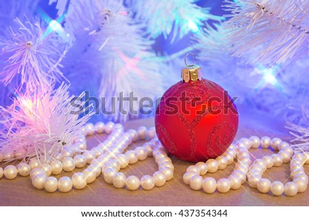 Red glass glitter Christmas bauble (decoration) with natural pearl garland (necklace) under the blue tinted Christmas tree with star shaped lights effect