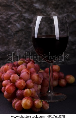 Red glass of wine and grapes on wooden table