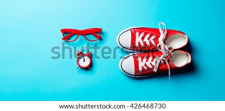 red glasses, clock and gumshoes on the blue background - stock photo