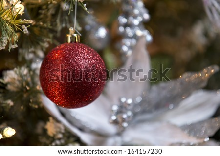 Red glitter ball ornament on Christmas tree