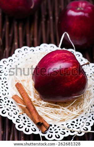 Red gloss apple on vintage white plate with cinnamon on a site.  - stock photo