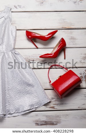 Red glossy shoes with purse. Luxury footwear on white table. Woman's bright-colored evening shoes. New collection in fashion house. - stock photo