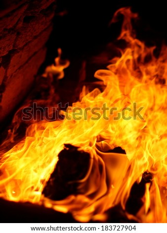 red glowing nature wood fuel in front of a vintage retro primitive ceramics kiln with yellow orange burning fire flame drawn along the brick wall into the kiln.  - stock photo