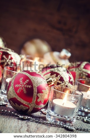 Red golden Christmas balls, burning candle and small beads on old wooden background, toned image, selective focus