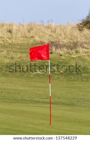Red golf flag on a seaside links course in the UK