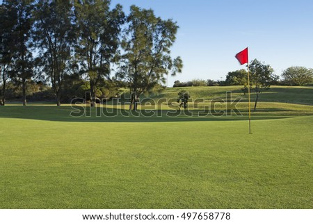 Red golf flag on golf course