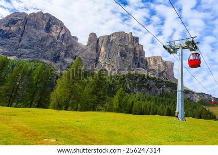 Red gondola cars on lift in Dolomites Mountains near Gardena Pass, Italy - stock photo