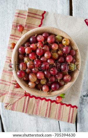 Red gooseberry in a bowl on wooden surface