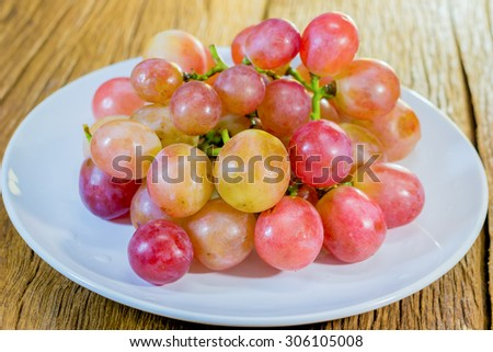 Red grape berries in white plate on old wooden floor.  - stock photo