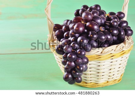 Red grape in basket on wooden table with copy space
