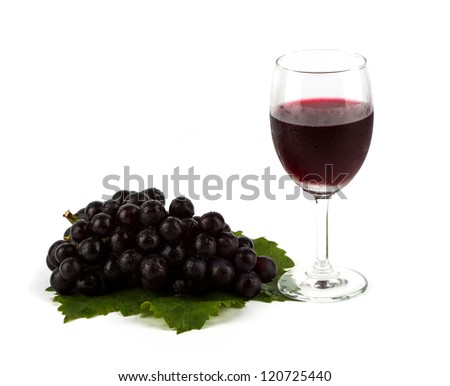 Red grape with green leaf  and a glass of red wine isolated on white background - stock photo