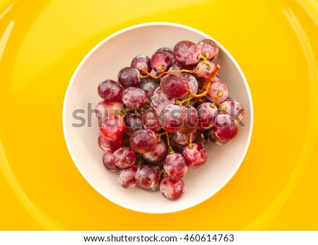 Red grapes in white bowl on yellow background