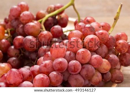 Red grapes on old wooden table,closeup background