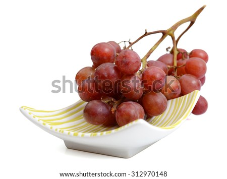 red grapes on plate isolated on white  - stock photo
