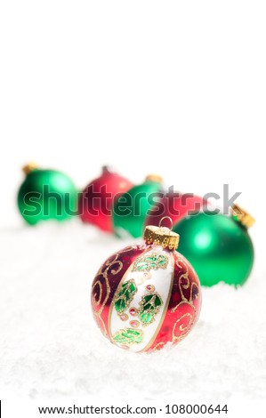 Red, green and colorful Christmas  baubles on snow