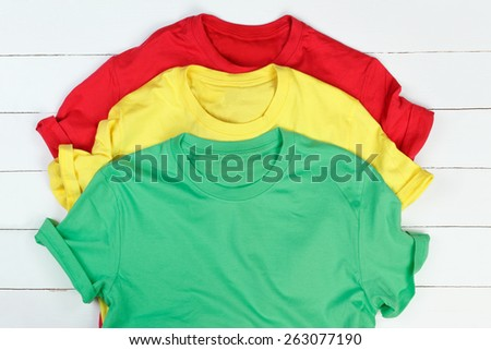 Red, green and yellow t-shirts on white wooden background