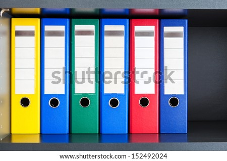 Red, green, blue and yellow office folders with boxes on the gray shelf - stock photo