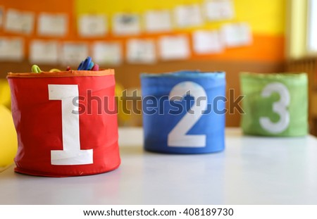 Red Green blue jars with large lettering one two and three on the table in the kindergarten class - stock photo