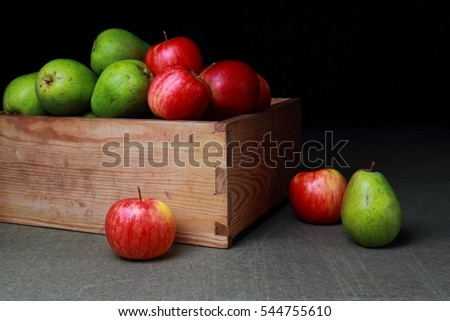 Red, green, sweet pear and an apple in an old wooden box on a dark background
