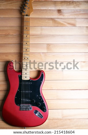 Red guitar on wooden background - stock photo