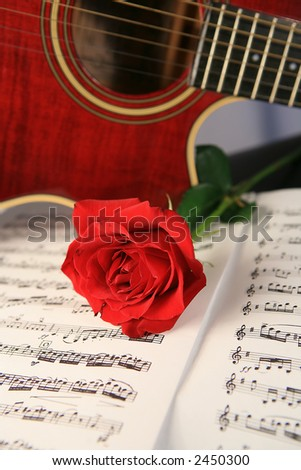 Red guitar with classical sheet music and red rose - stock photo