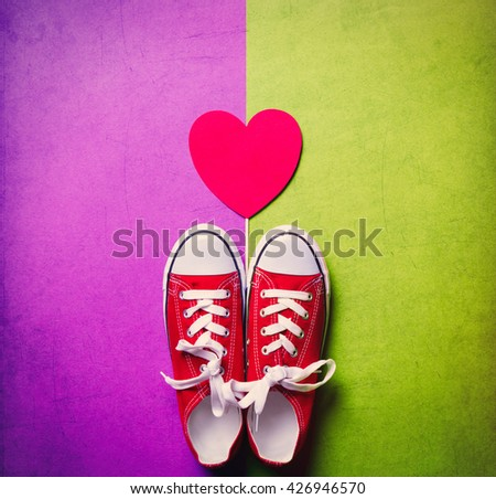 red gumshoes and heart shaped toy on the purple and green background