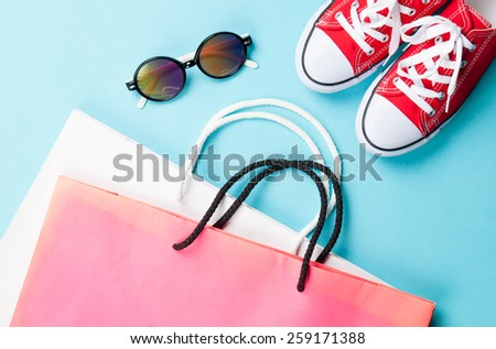 Red gumshoes with shopping bags and sunglasses on blue background. - stock photo
